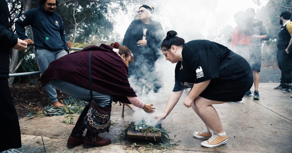 Smoking ceremony with two people placing gum leaves into the fire
