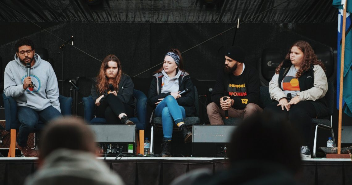 Four young people sitting on a stage on a panel