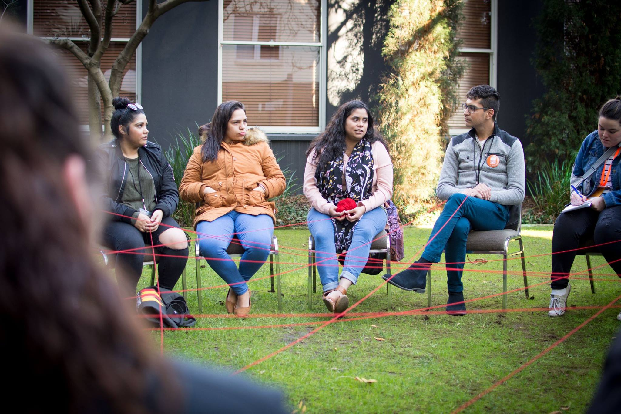 young people sitting around in a circle yarning