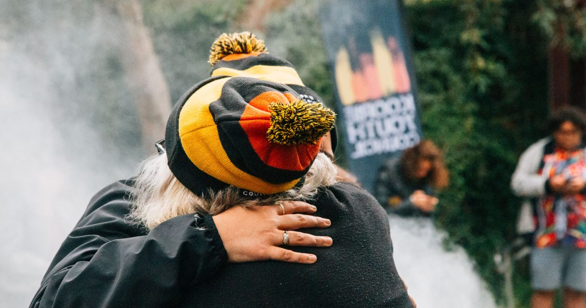 Two people embracing with two beanies with the Aboriginal flag colours
