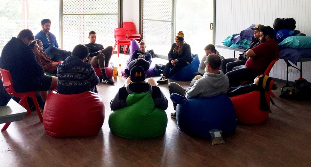 a group of young people meditating in a circle