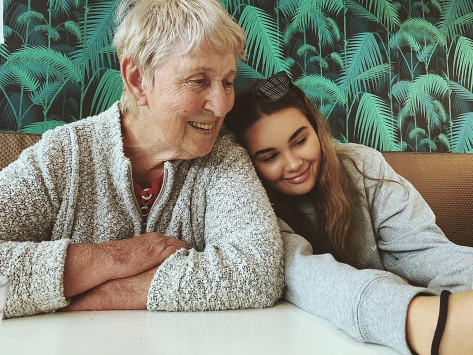 An older woman smiling with a younger woman resting her head on her shoulder. They are sitting down at a table in front of a wall covered in palm tree images.