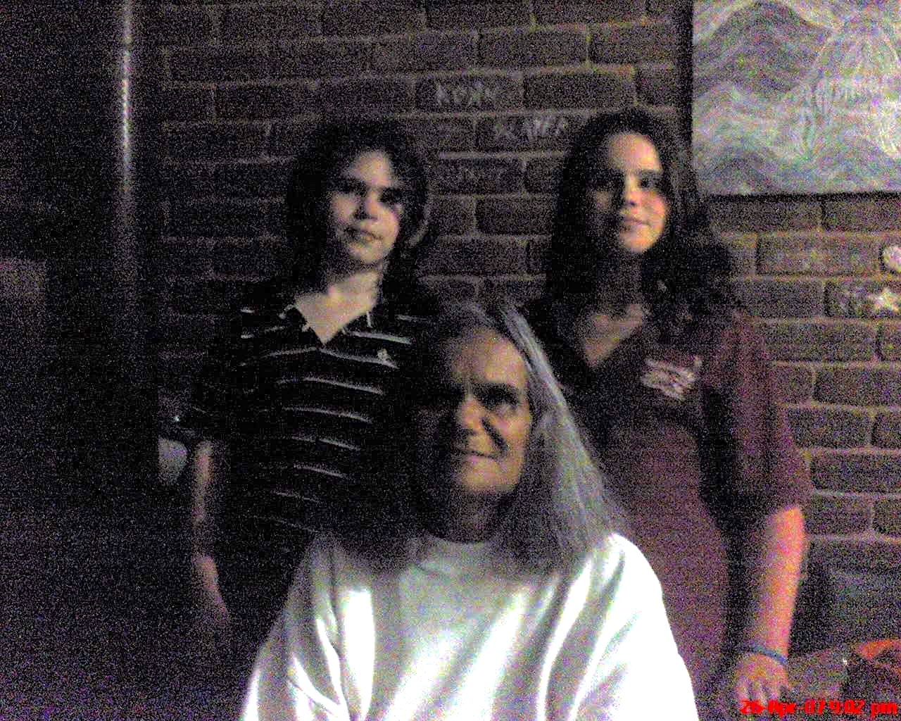 Two young people standing behind an older woman against a brick wall with a picture frame hanging on it. All three people are smiling.