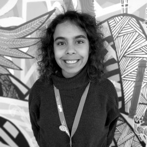 Young woman smiling standing in front of colourful Aboriginal mural